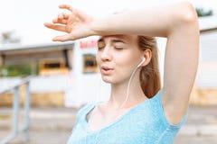 女孩由健身做在训练的一个断裂,休息和赛跑在路 库存照片