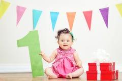 女孩由堆礼物坐生日聚会 免版税库存照片
