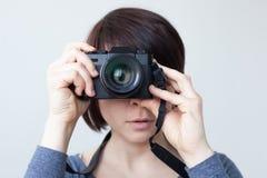 女孩由她的面孔拿着一台照相机 免版税库存照片