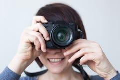 女孩由她的面孔拿着一台照相机 免版税库存图片