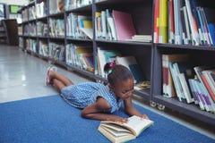 女孩由架子的阅读书在图书馆里 免版税库存图片