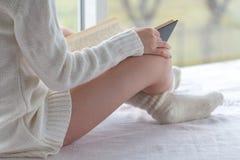 女孩由窗口的阅读书 免版税库存照片