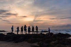 女孩男孩家庭现出轮廓的海滩海洋日出 免版税图库摄影