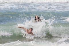 女孩男孩抓住波浪海滩 免版税库存照片