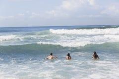 女孩男孩游泳挥动海滩 免版税库存图片