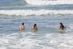 女孩男孩游泳海滩 免版税库存照片