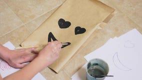 女孩画与在纸袋各种各样的情感的一把刷子 情感的概念在面带笑容的 免版税库存图片