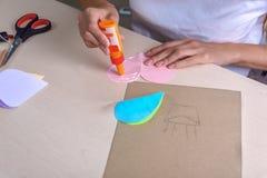 女孩画与坐在桌上的蜡笔 免版税库存照片