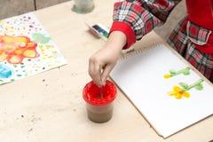 女孩画与油漆的一张图画在板料 免版税库存照片