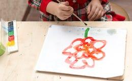女孩画与油漆的一张图画在板料 库存照片