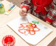 女孩画与油漆的一张图画在板料 免版税图库摄影