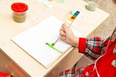女孩画与油漆的一张图画在板料 免版税库存图片