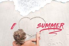 女孩画在沙子的心脏 免版税库存图片
