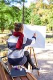 女孩画在画架的红色油漆 免版税库存图片