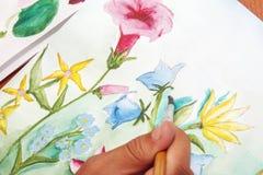 女孩画在白皮书的美丽的野花 免版税库存照片