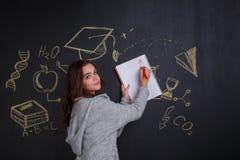 女孩画在笔记本的一个箭头,站立在一个委员会的背景有科学的标志的图象的和 库存图片