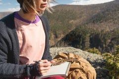 女孩画家画在一个笔记本的一支铅笔在山的自然 自由创造性和做自由职业者 图库摄影