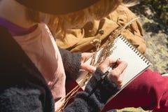 女孩画家画在一个笔记本的一支铅笔在山的自然 自由创造性和做自由职业者 库存图片