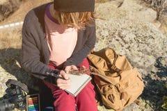 女孩画家画在一个笔记本的一支铅笔在山的自然 自由创造性和做自由职业者 免版税图库摄影