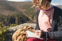女孩画家画在一个笔记本的一支铅笔在山的自然 自由创造性和做自由职业者 库存照片