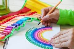 女孩画彩虹 正面图画 艺术疗法和relaxati 免版税图库摄影