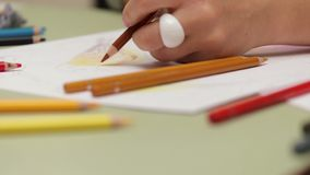 女孩画用左手与在纸,在慢动作的详细的看法的色的铅笔 股票录像