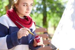 女孩画红色在画架的油漆特写镜头 库存照片