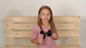 女孩画象一件桃红色礼服的在演播室,她坐长木凳 股票录像