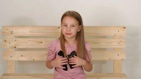 女孩画象一件桃红色礼服的在演播室,她坐长木凳 影视素材