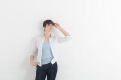 女孩画象一件白色衬衣和牛仔布牛仔裤的有在白色背景的太阳镜的 库存照片