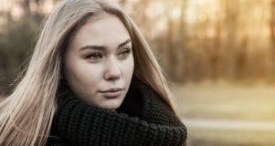女孩画象以秋天公园为背景的 库存图片