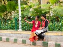 女孩画象传统上穿戴了采取在智能手机的selfie 免版税库存图片