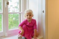 女孩画象桃红色礼服的坐窗口基石 图库摄影