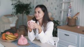 女孩画象浴巾的在厨房,饮料茶,慢动作里享受早晨时间 股票录像