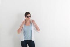 女孩画象牛仔裤和太阳镜的有拿着一个白色衬衣衣领的短发的 免版税库存图片