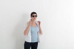 女孩画象牛仔裤和太阳镜的有拿着在白色背景的短发的一个白色衬衣衣领 免版税库存照片