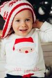 女孩画象被编织的帽子和毛线衣的有圣诞老人的 库存照片
