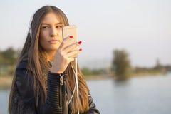 女孩画象,当坐通过河和听时 免版税库存图片