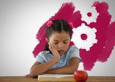 女孩疲倦了在有苹果和设置嵌齿轮齿轮的书桌 库存照片