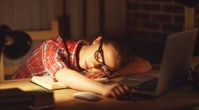 女孩疲倦的学生在家睡着了在计算机 免版税图库摄影