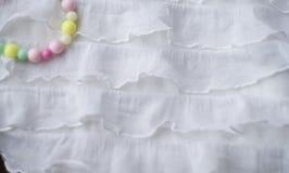 女孩的Ð ¡ olorful串珠的镯子白色波浪织地不很细纺织品的 图库摄影