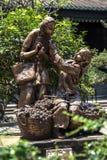 女孩的一个古铜色雕象的雕象卖果子荔枝的 库存照片