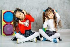女孩的两个女孩跳舞并且听到耳机音乐 库存照片