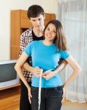 女孩的人测量的腰部有测量的磁带的 库存照片