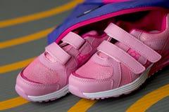 女孩的儿童的运动鞋和在地毯的背包谎言 图库摄影