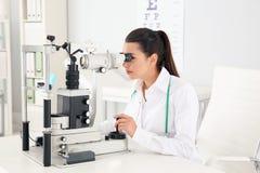 女孩的医生与眼科设备一起使用 免版税库存图片