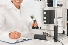 女孩的医生用眼科设备在办公室 免版税库存图片