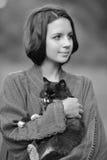 女孩的单色画象有一只猫的在她的胳膊 免版税库存照片