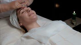 女孩的平均计划谈话在面部护肤期间在整容术中心 美容师的手投入了一个滋补哥斯达黎加 股票视频