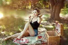 女孩的性感的别针有在短的夏天布料的白肤金发的曲线头发的在野餐 免版税库存照片